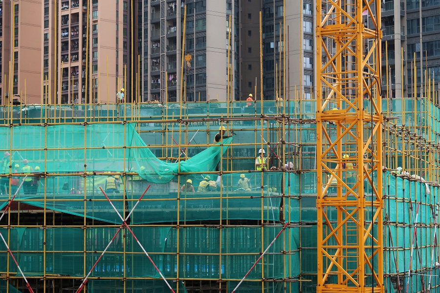 Workers are seen on scaffoldings of a construction site near residential buildings in Shenzhen, Guangdong province, China, 17 May 2020. (Martin Pollard/File Photo/Reuters)