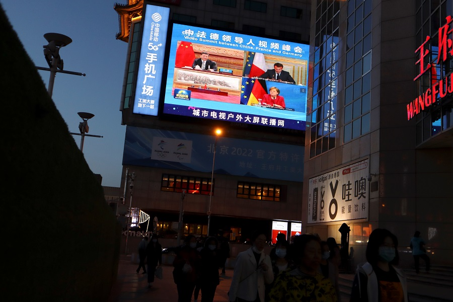 A giant screen shows news footage of Chinese President Xi Jinping attending a video summit on climate change with German Chancellor Angela Merkel and French President Emmanuel Macron, at a shopping street in Beijing, China, 16 April 2021. (Florence Lo/Reuters)