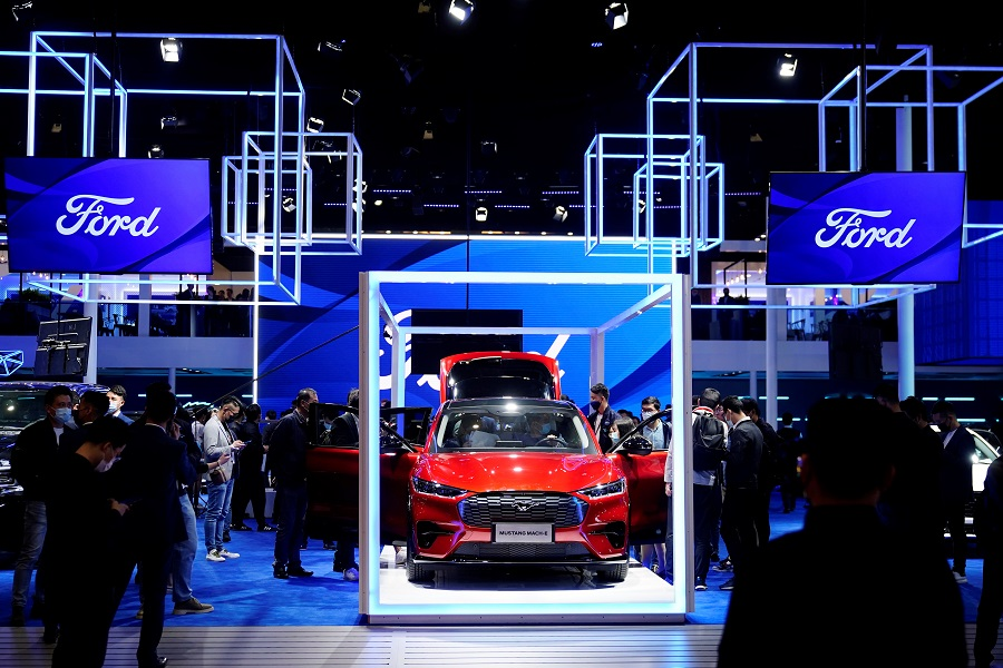 Visitors check a Ford Mustang Mach-E electric vehicle (EV) displayed at the Ford booth during a media day for the Auto Shanghai show in Shanghai, China, 19 April 2021. (Aly Song/Reuters)