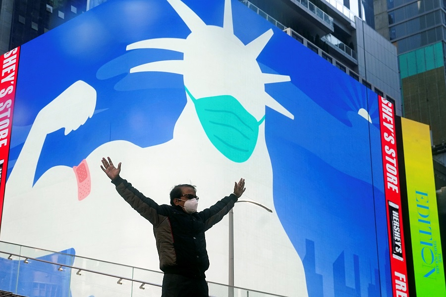 A man poses for a photo on the Red Steps in Times Square as an image of the Statue of Liberty wearing a mask is projected on a billboard amid the Covid-19 pandemic in the Manhattan borough of New York City, New York, US, 20 April 2021. (Carlo Allegri/Reuters)