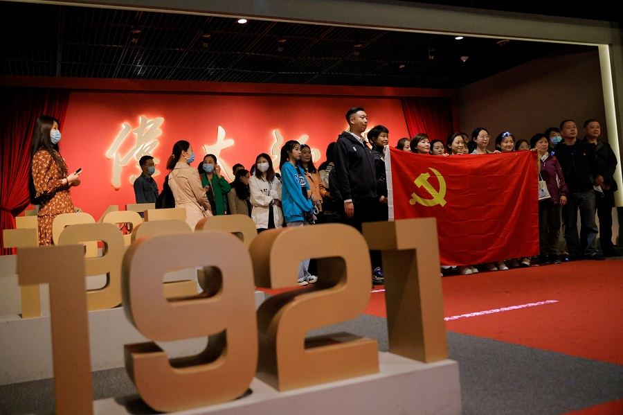 People hold the Chinese national flag as they pose for a group picture at an exhibition marking the 100th founding anniversary of the Chinese Communist Party (CCP) in Beijing, China, 22 April 2021. (Thomas Peter/Reuters)