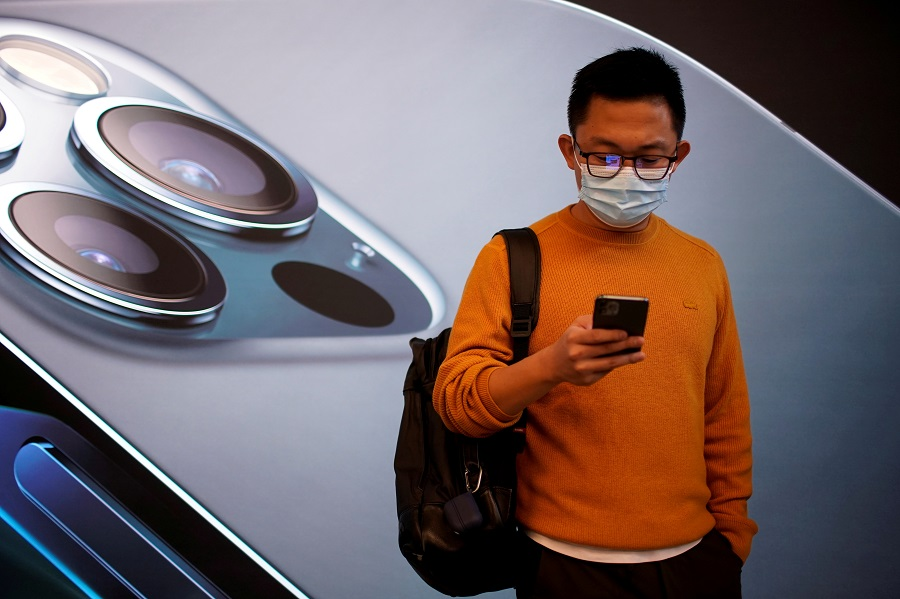 A man wears a face mask while waiting at an Apple Store before Apple's new iPhone 12 goes on sale in Shanghai, China, 23 October 2020. (Aly Song/File Photo/Reuters)