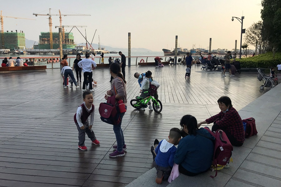 Children play at a waterfront in Shekou area of Shenzhen, Guangdong province, China, 15 March 2021. (David Kirton/Reuters)
