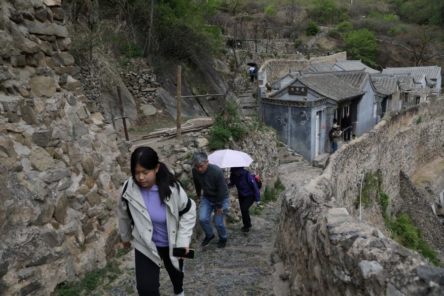 People walk at a historic village which is now a tourist attraction during the 5-day Labour Day holiday in the suburbs of Beijing, China, 4 May 2021. (Tingshu Wang/Reuters)