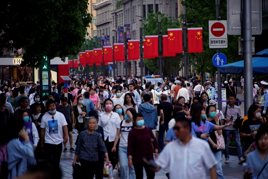 People walk along Nanjing Road, a main shopping area, in Shanghai, China, 10 May 2021. (Aly Song/Reuters)