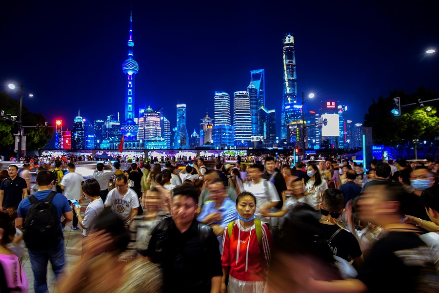 People walk near the Bund, in front of Lujiazui financial district of Pudong, Shanghai, China, 10 May 2021. (Aly Song/Reuters)