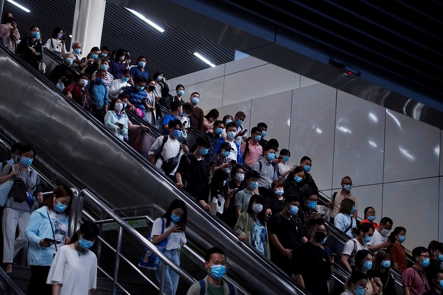 People walk at a subway station in Shanghai, China, 11 May 2021. (Aly Song/Reuters)