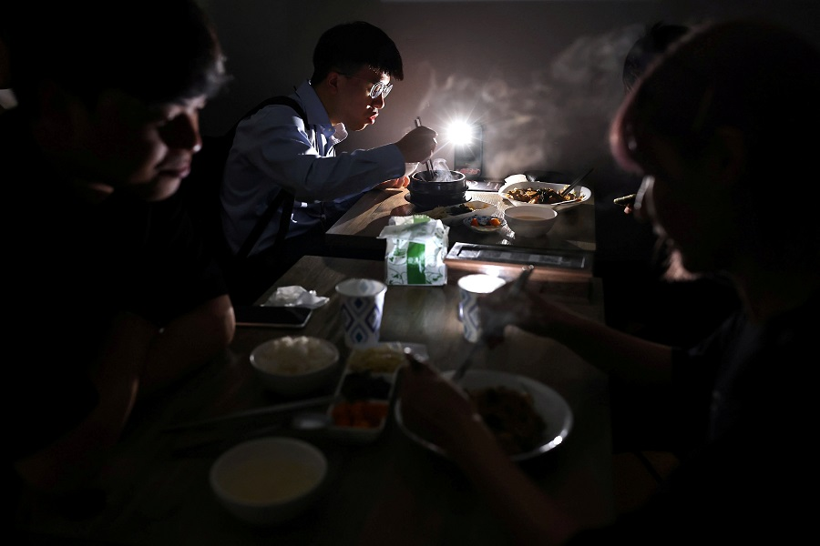 People eat using the light from their phone while experiencing a blackout due to a power outage, in Taipei, Taiwan, 13 May 2021. (Ann Wang/Reuters)