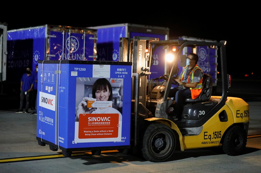 A worker transports a container carrying a batch of China's Sinovac Covid-19 vaccine at the Oscar Arnulfo Romero International Airport in San Luis Talpa, El Salvador, 18 May 2021. (Jose Cabezas/Reuters)