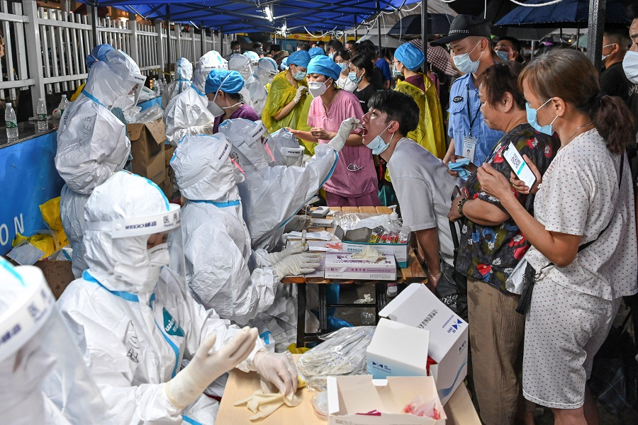 A medical worker collects a swab from a resident during a mass testing for the Covid-19 coronavirus disease at a makeshift testing site in Guangzhou, Guangdong province, China, 30 May 2021. (CNS photo via Reuters)