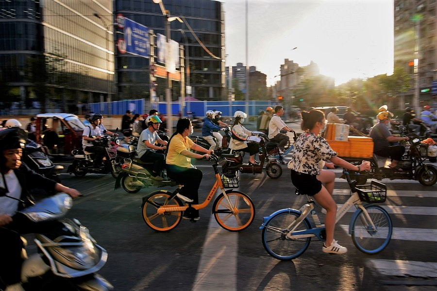 People ride bicycles and motorbikes on a street, in Shanghai, China, 31 May 2021. (Aly Song/Reuters)