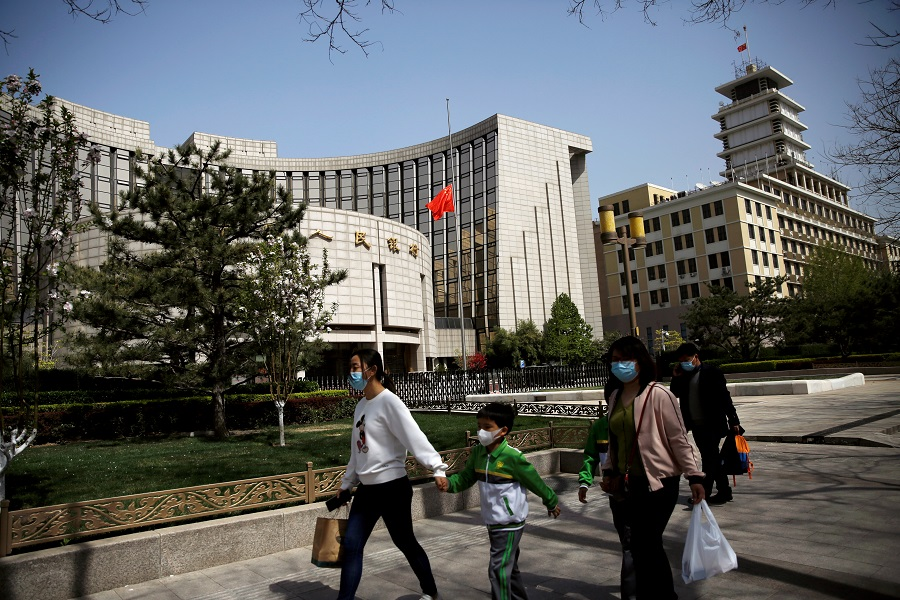 People wearing face masks walk past the headquarters of the People's Bank of China (PBOC), 4 April 2020. (Tingshu Wang/File Photo/Reuters)