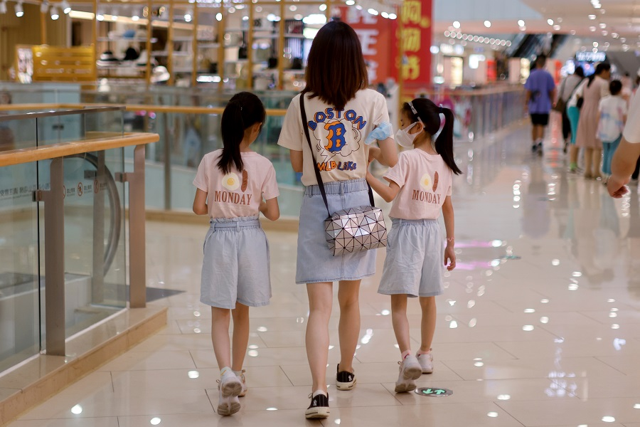 A mother walks with her daughters at a shopping mall in Shanghai, China, 1 June 2021. (Aly Song/Reuters)