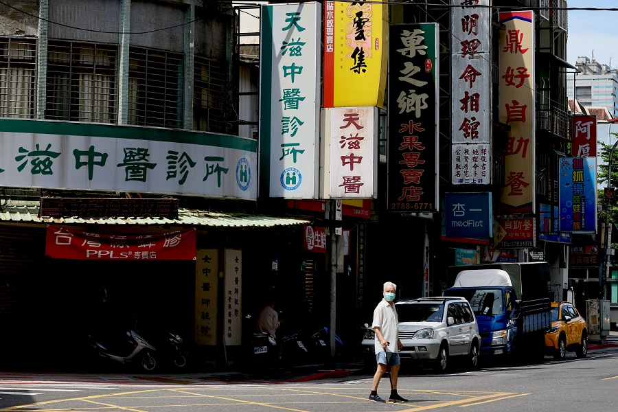 A man crosses the street while wearing a protective mask in Taipei, Taiwan, 2 June 2021. (Ann Wang/Reuters)