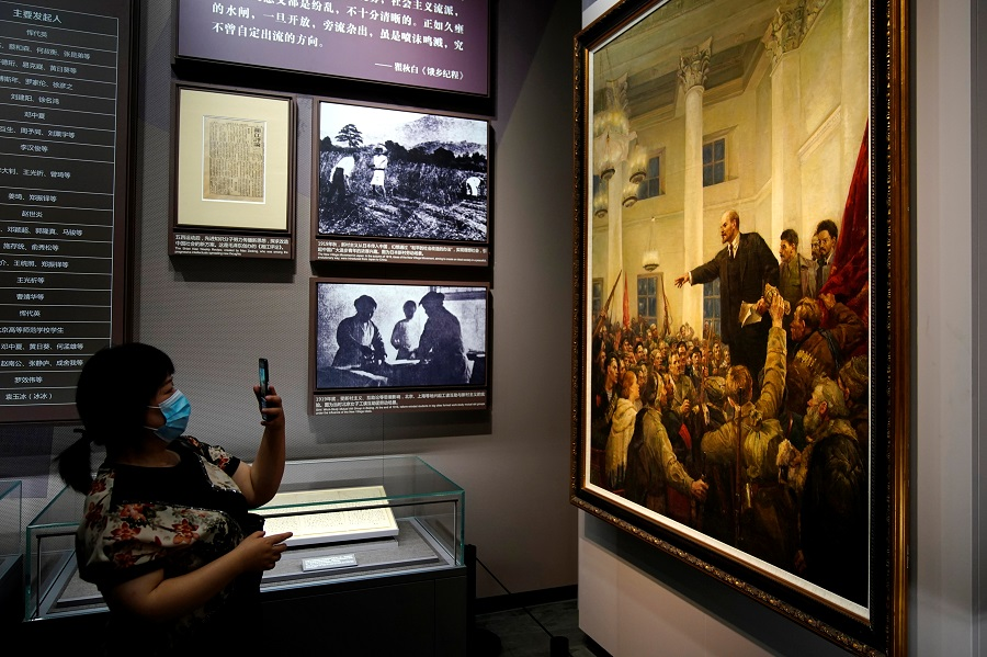 A woman takes a picture of Lenin in a painting during an event marking the 100th founding anniversary of the Communist Party of China at the Memorial of the First National Congress of the Communist Party of China in Shanghai, China, 4 June 2021. (Aly Song/Reuters)
