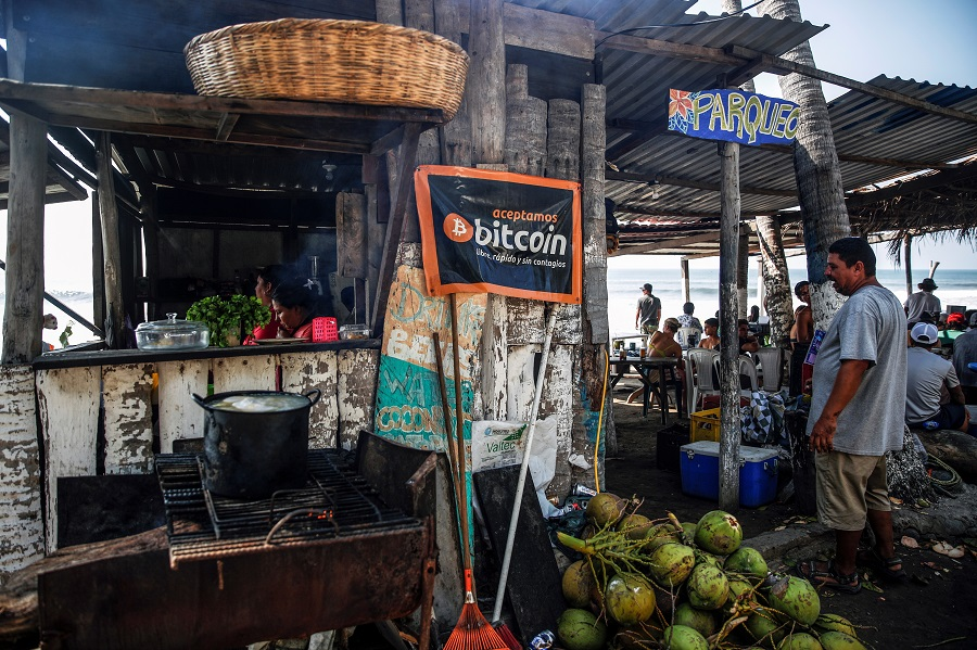 """A banner that reads """"We accept Bitcoin, free, fast and without contagion"""" is seen at a beach cafe on Punta Roca Beach in La Libertad, El Salvador, 25 April 2021. (Jose Cabezas/Reuters)"""