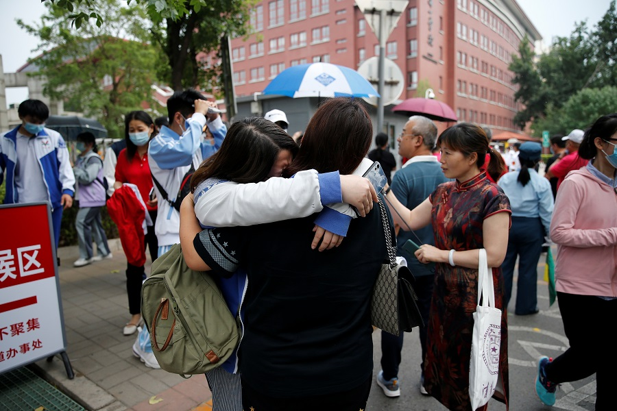A student hugs her family member after an exam as part of the annual national college entrance exam, or gaokao, in Beijing, China, 7 June 2021. (Tingshu Wang/Reuters)