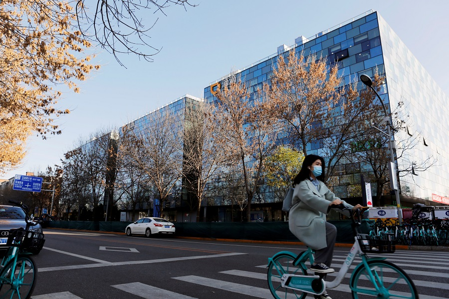 A woman rides a Didi shared bicycle past the headquarters of Didi Chuxing in Beijing, China, 20 November 2020. (Florence Lo/File Photo/Reuters)
