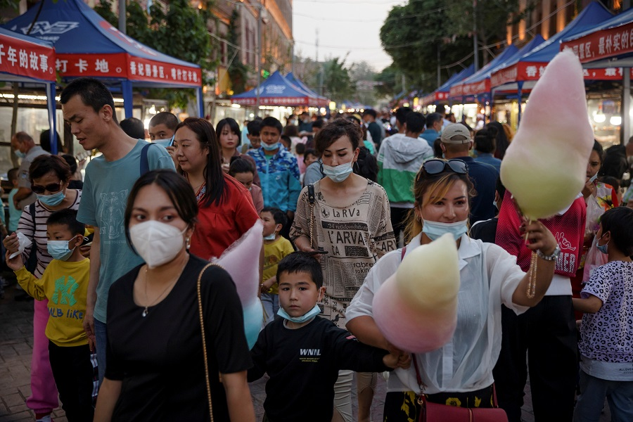 People walk in a night market during the Labour Day holidays tourist rush in the old city in Kashgar, Xinjiang Uighur Autonomous Region, China, 2 May 2021. (Thomas Peter/Reuters)
