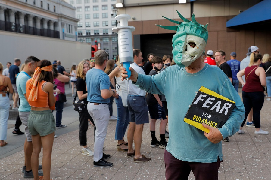 An anti-vaccine protester dressed as the Statue of Liberty holding an oversized syringe attends a gathering outside Madison Square Garden ahead of a Foo Fighters' show, which required proof of vaccination to enter, in New York City, US, 20 June 2021. (Andrew Kelly/Reuters)