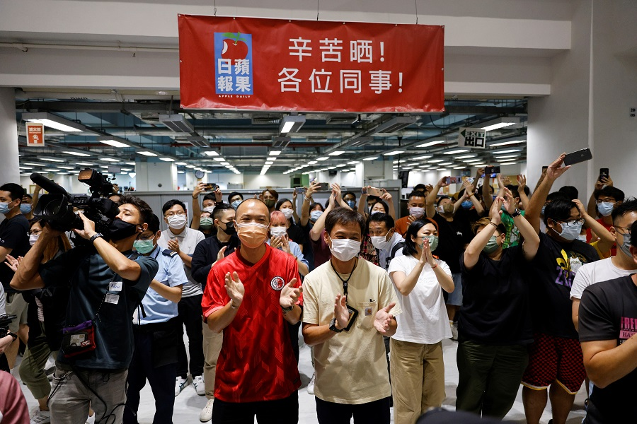 Staff members of Apple Daily and its publisher Next Digital react on the day of the newspaper's final edition in Hong Kong, China, 23 June 2021. (Tyrone Siu/Reuters)