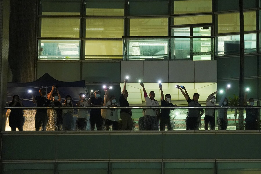 Staff light their phone flashlights and wave to supporters at the headquarters of the Apple Daily newspaper, and its publisher Next Digital, after the announcement that it will print its last edition, in Hong Kong, China, 23 June 2021. (Lam Yik/Reuters)