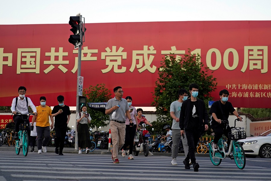 People walk on a street in front of a signboard marking the 100th founding anniversary of the Communist Party of China, ahead of the 100th anniversary of the Communist Party of China, in Shanghai, China, 22 June 2021. (Aly Song/Reuters)