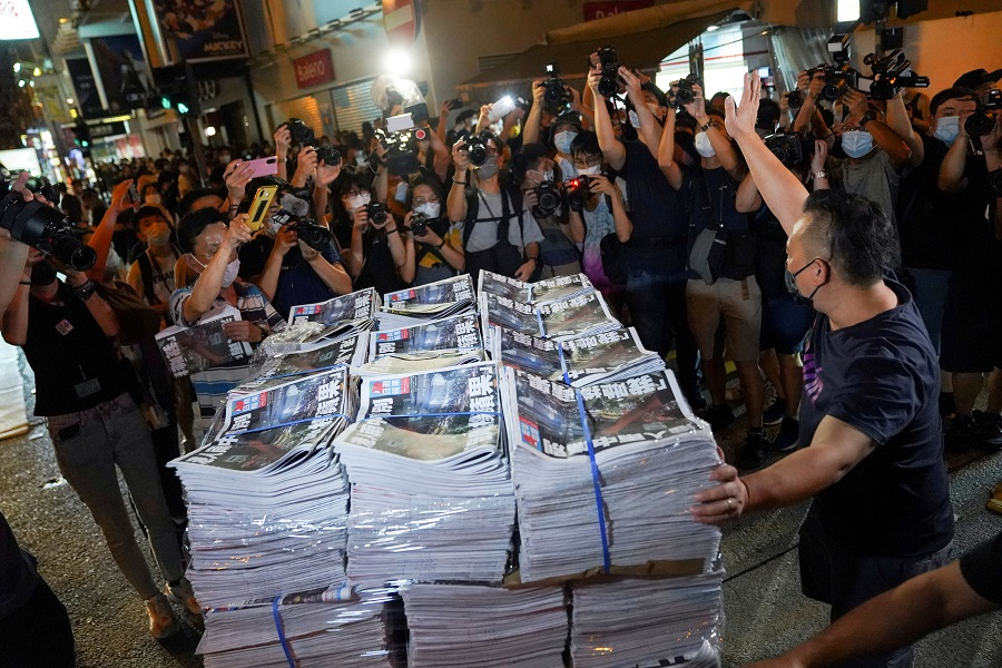 A man gestures as he brings copies of the final edition of Apple Daily, published by Next Digital, to a news stand in Hong Kong, China, 24 June 2021. (Lam Yik/File Photo/Reuters)
