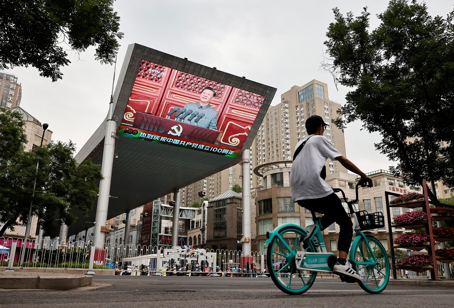 A man cycles in front of a screen showing Chinese President Xi Jinping speaking during a celebration marking the 100th founding anniversary of the Communist Party of China, in Beijing, China, 1 July 2021. (Thomas Peter/Reuters)