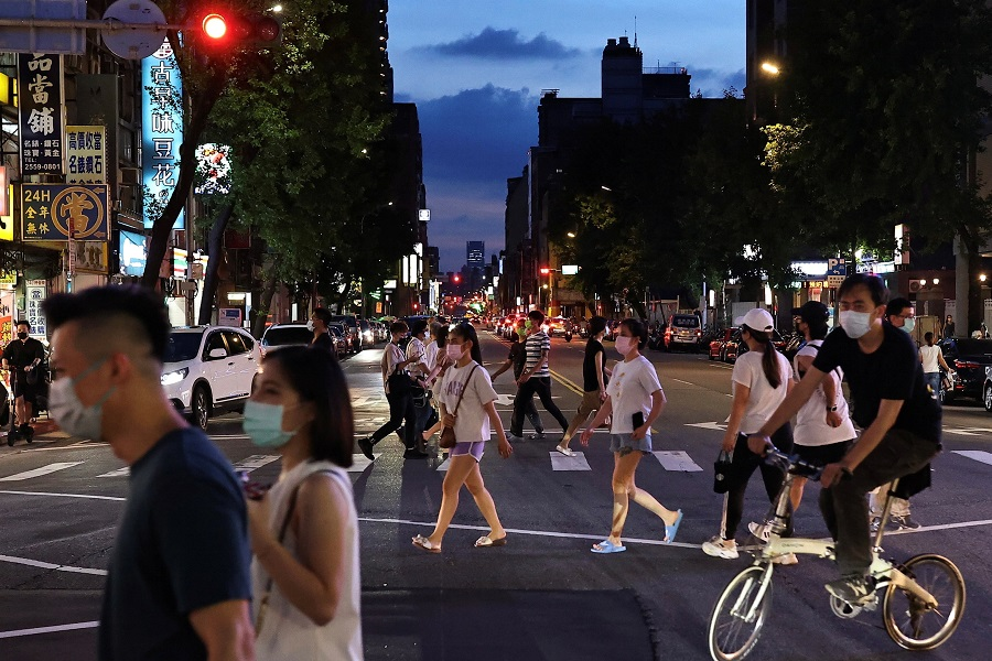 People wearing protective masks cross the road to the newly opened night market in Taipei, Taiwan, 2 July 2021. (Ann Wang/Reuters)