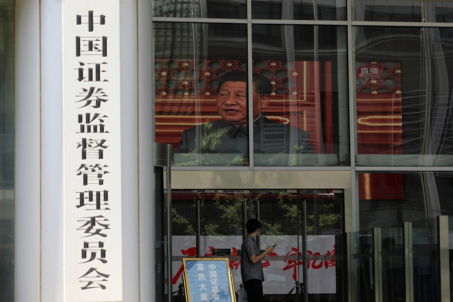 A man stands near a screen showing news footage of Chinese President Xi Jinping at the China Securities Regulatory Commission (CSRC) building on the Financial Street in Beijing, China, 9 July 2021. (Tingshu Wang/Reuters)