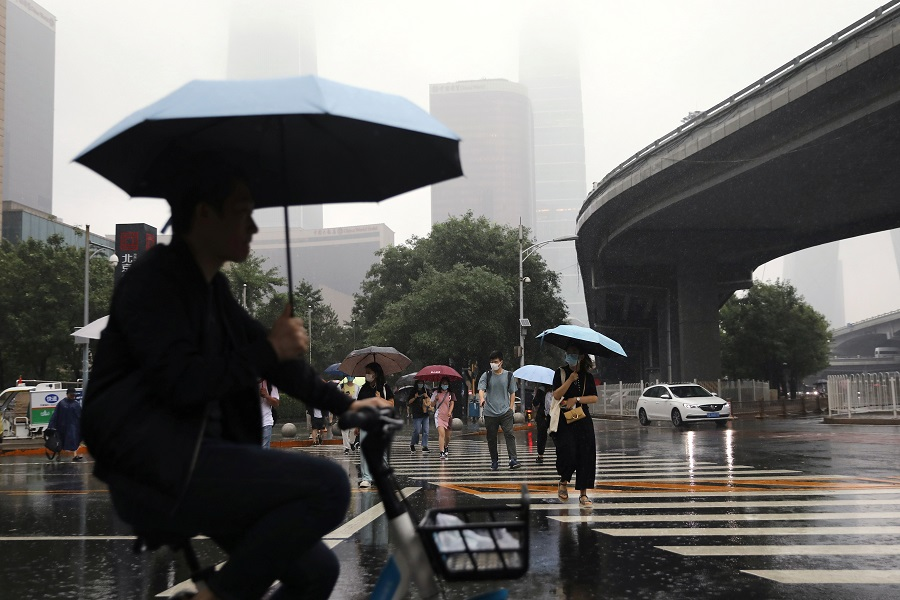People are seen amid heavy rainfall during morning rush hour in Beijing's Central Business District, China, 12 July 2021. (Tingshu Wang/Reuters)