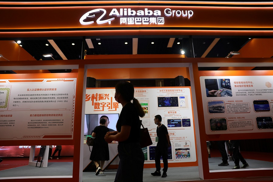 People walk past a booth of Alibaba Group at an exhibition during the China Internet Conference in Beijing, China, 13 July 2021. (Tingshu Wang/Reuters)