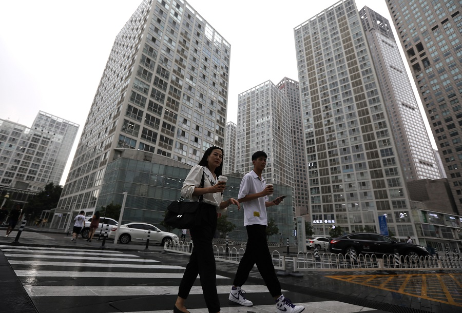 People walk past an office compound in Beijing's Central Business District, China, 13 July 2021. (Tingshu Wang/Reuters)