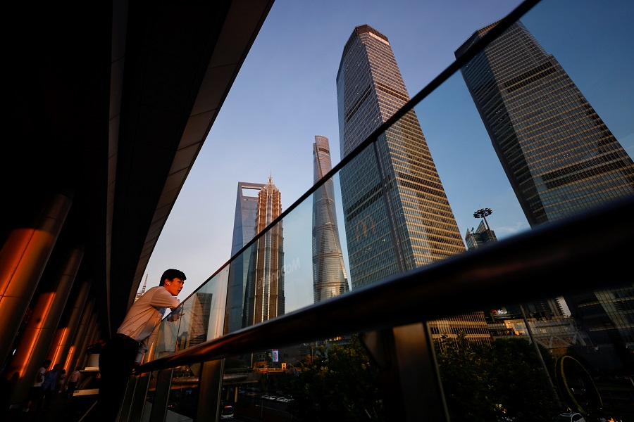 A man makes a call through the headset in the Lujiazui financial district during sunset in Pudong, Shanghai, China, 13 July 2021. (Aly Song/Reuters)