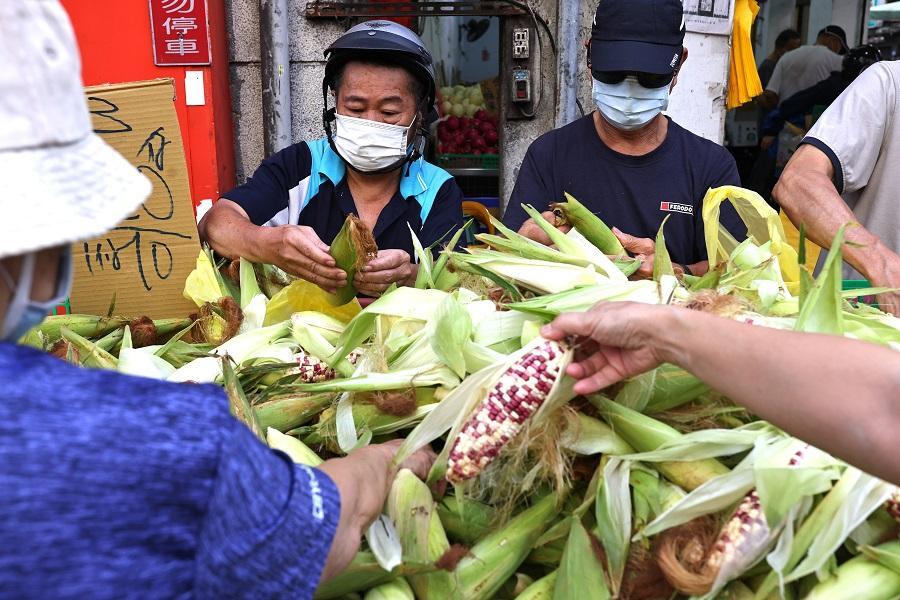 Customers wearing protective face masks shop at a market in Taipei, Taiwan, 16 July 2021. (Ann Wang/Reuters)