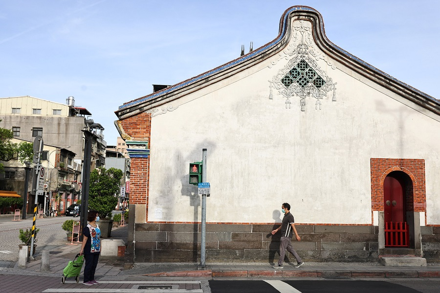People wearing protective face masks walk past a temple in Taipei, Taiwan, 16 July 2021. (Ann Wang/Reuters)