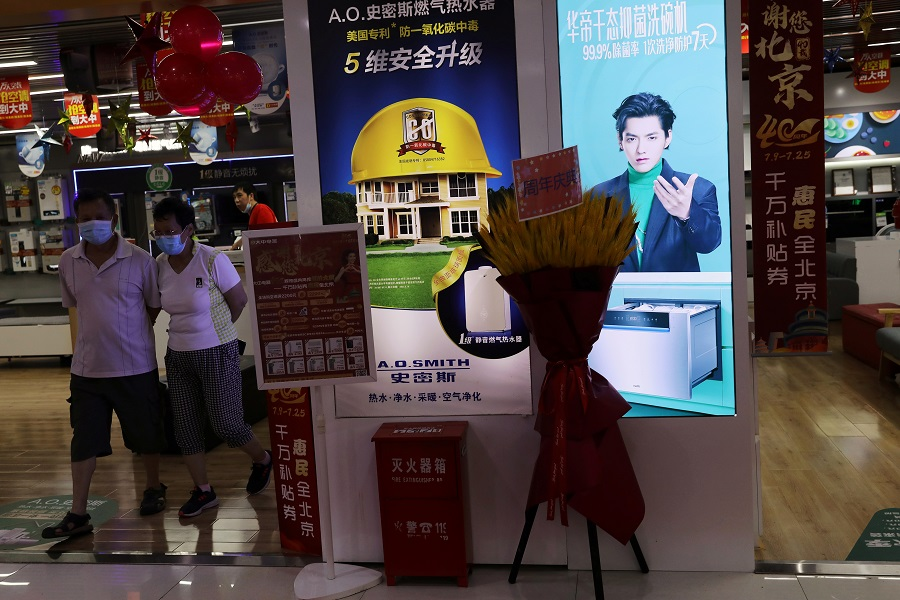 People walk next to a home appliances store displaying an advertisement that features singer-actor Kris Wu, at a shopping mall in Beijing, China, 20 July 2021. (Tingshu Wang/Reuters)