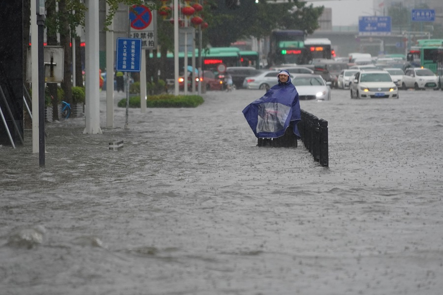 A resident wearing a rain cover stands on a flooded road in Zhengzhou, Henan province, China, 20 July 2021. (CNS photo via Reuters)