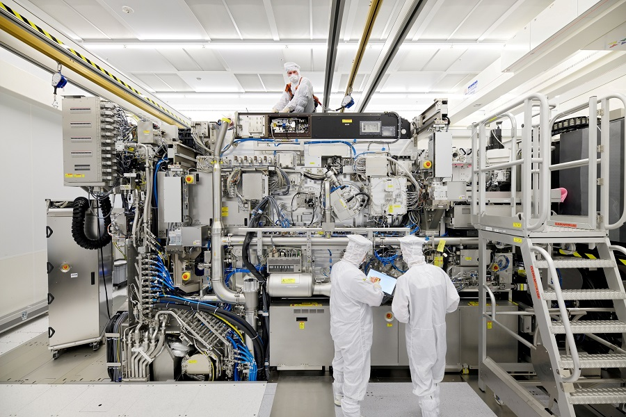Employees are seen working on the final assembly of ASML's TWINSCAN NXE:3400B semiconductor lithography tool with its panels removed, in Veldhoven, Netherlands, in this picture taken on 4 April 2019. (Bart van Overbeeke Fotografie/ASML/Handout via Reuters)