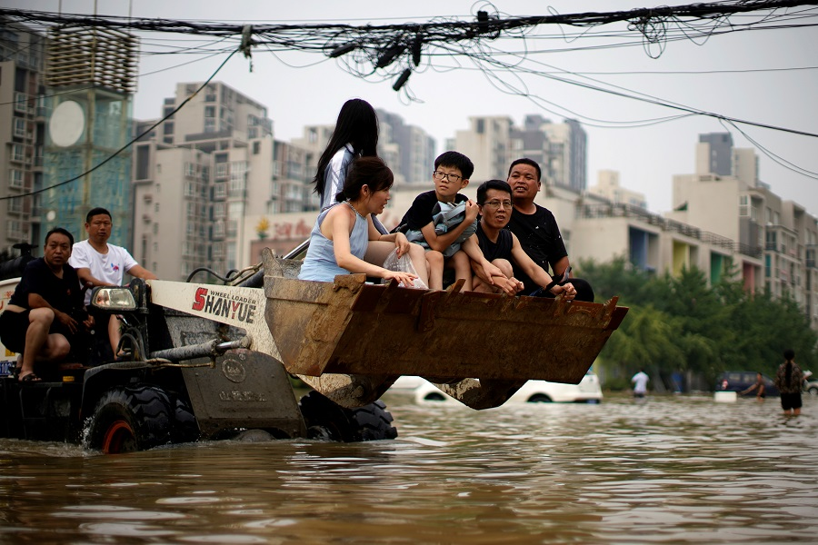 People ride on a front loader as they make their way through floodwaters following heavy rainfall in Zhengzhou, Henan province, China, 23 July 2021. (Aly Song/File Photo/Reuters)