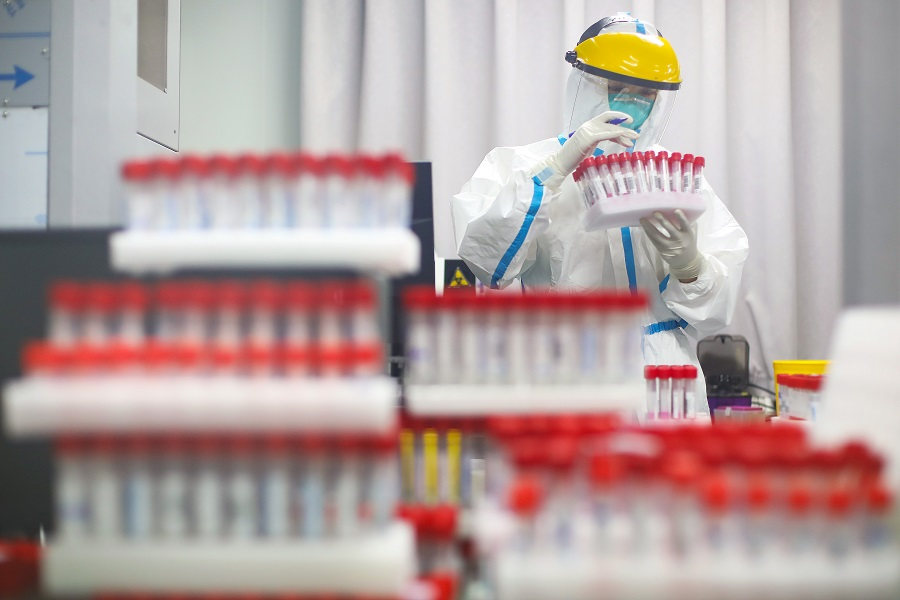 A medical staff in protective suit works at a nucleic acid testing laboratory of Nanjing First Hospital in Nanjing, Jiangsu province, China, 24 July 2021. (CNS photo via Reuters)