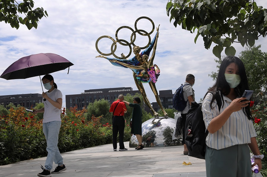 Visitors are seen next to a sculpture featuring skates outside the headquarters of the Beijing Organising Committee for the 2022 Olympic and Paralympic Winter Games in Beijing, China, 30 July 2021. (Tingshu Wang/Reuters)