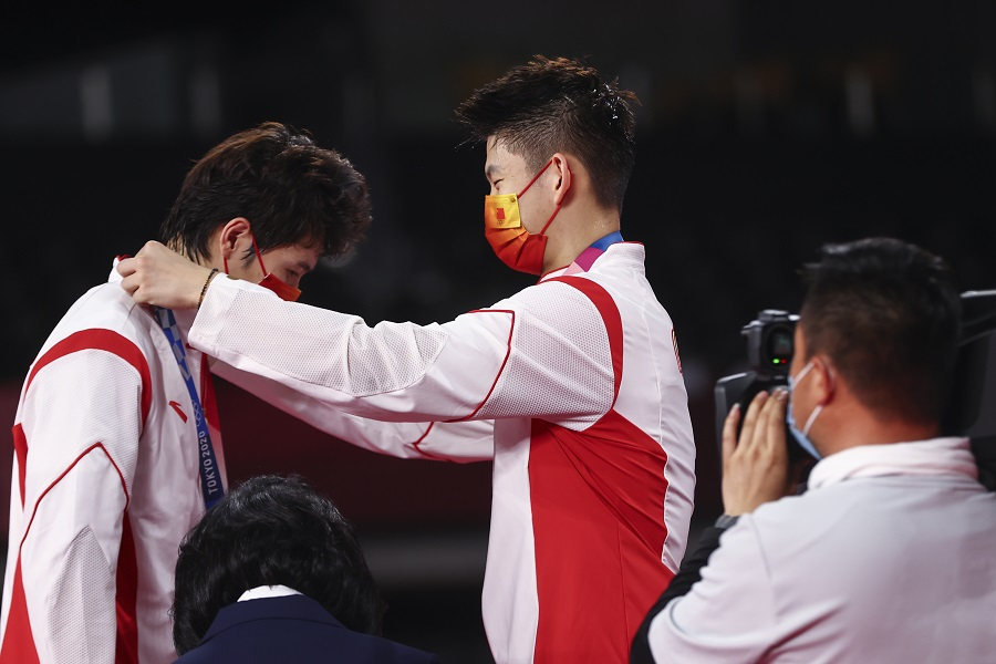 Silver medallist Liu Yuchen of China places the medal on teammate Li Junhui of China at the badminton men's doubles medal ceremony, Musashino Forest Sport Plaza, Tokyo, Japan, 31 July 2021. (Leonhard Foeger/Reuters)