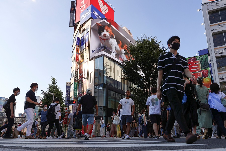 Passersby wearing protective face masks walks on the street at Shinjuku district in Tokyo, Japan, 1 August 2021. (Issei Kato/Reuters)