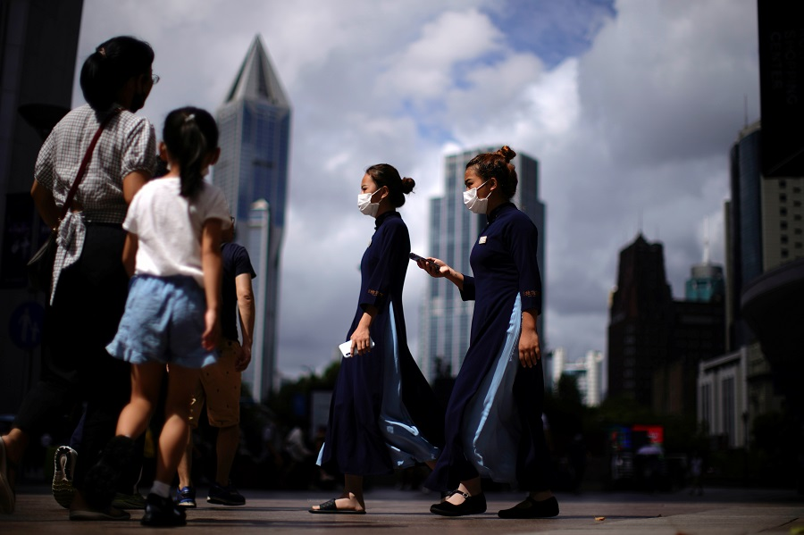 People wearing protective masks walk on a street in Shanghai, China, 5 August 2021. (Aly Song/Reuters)