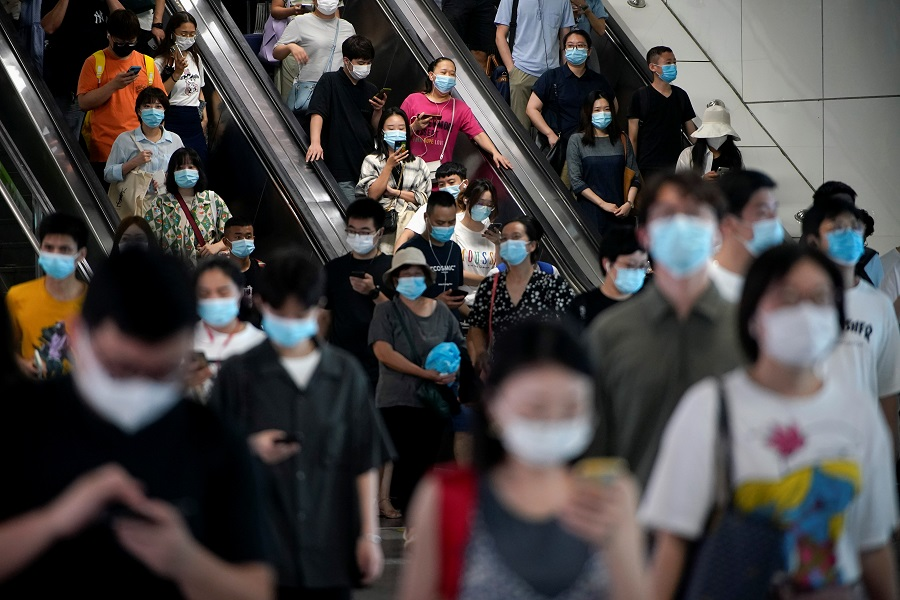 People wearing protective masks ride escalators inside a subway station in Shanghai, China, 5 August 2021. (Aly Song/Reuters)