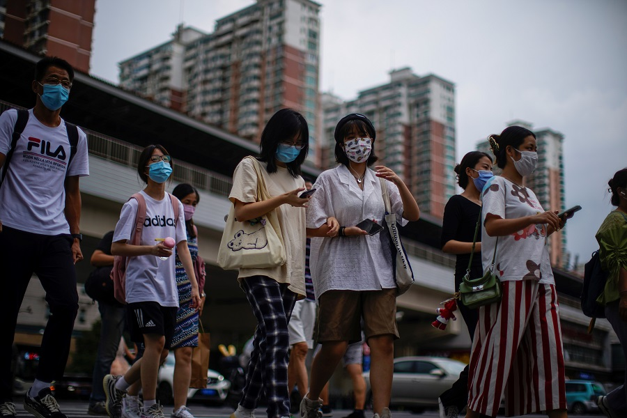 People wearing protective masks walk on a street in Shanghai, China, 10 August 2021. (Aly Song/Reuters)