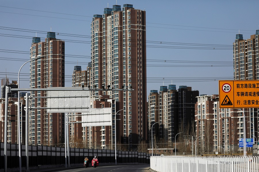 People ride scooters past residential buildings in Beijing, China, 13 January 2021. (Tingshu Wang/File Photo/Reuters)