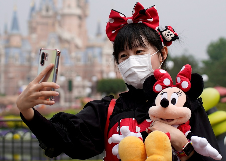 A visitor dressed as a Disney character takes a selfie while wearing a protective face mask at Shanghai Disney Resort in Shanghai, China, 11 May 2020. (Aly Song/File Photo/Reuters)